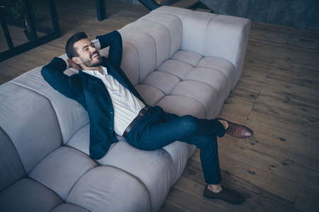 Portrait of his he nice attractive luxurious successful cheerful cheery glad bearded guy wearing jacket blazer sitting on cozy divan at home house flat apartment open space indoors