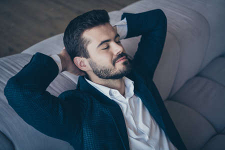 Close-up portrait of his he nice attractive luxurious well-groomed dreamy bearded guy wearing jacket blazer resting on divan closed eyes at home house flat indoors