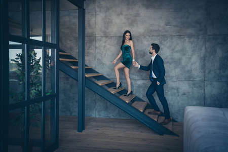 Full length profile photo of tender stylish trendy couple guy lady desire climbing up second floor holding hands new house excursion wear formalwear suit short dress loft industrial indoors