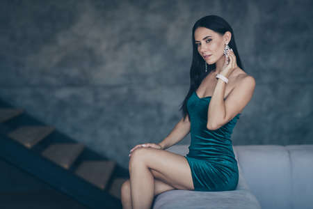 Profile photo of tenderness lady sitting on comfy modern sofa remembering last ideal love night touch earring ear wear formalwear shiny short mini dress apartments indoors