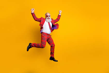 Full length body size view of nice handsome attractive cheerful cheery, funky comic gray-haired man jumping having fun rejoice isolated over bright vivid shine vibrant yellow color background