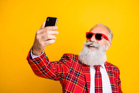 Closeup photo of cool grandpa white beard guy holding telephone, taking funny selfies wear sun specs checkered red blazer tie outfit isolated yellow color background