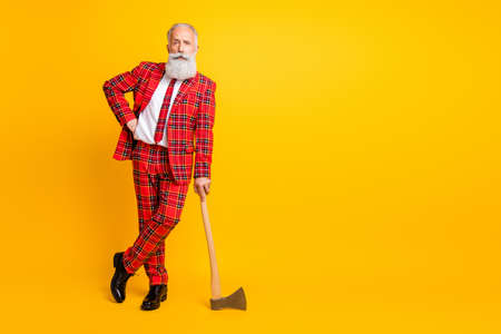 Full length photo of cool aged guy white beard holding ax hands play serial killer character at halloween wear tartan red costume outfit isolated bright yellow color background