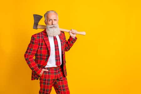 Foto von coolem weißen Bart des Großvaters, der große Axthände hält, die bei Halloween eine Serienmörderrolle spielen, tragen kariertes rotes Kostümoutfit isoliert hellgelber Farbhintergrund