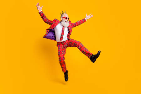 Full length body size view of his he nice handsome attractive cheerful cheery carefree gray-haired man jumping having fun rejoice isolated over bright vivid shine vibrant yellow color background Stockfoto