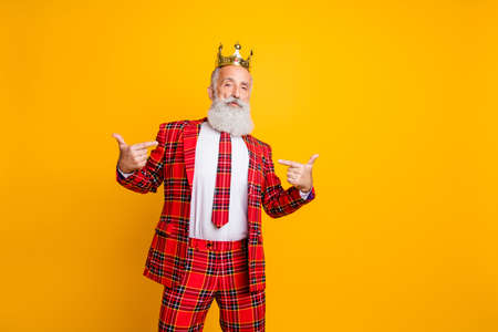 Das bin ich. Foto von coolem Look Opa weißer Bart hochmütige Person, die mit den Fingern selbst zeigt, trägt Krone karierten roten Anzug Kleidung isoliert gelber Hintergrund