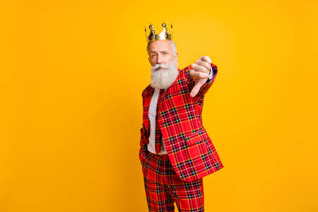 Portrait of his he nice handsome attractive proud serious gray-haired man wearing crown showing thumb down isolated over bright vivid shine vibrant yellow color background Zdjęcie Seryjne