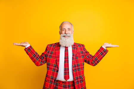 Photo of funny grandpa guy holding open palms empty space two novelty products wear lumberjack suit red blazer tie outfit isolated bright yellow color background