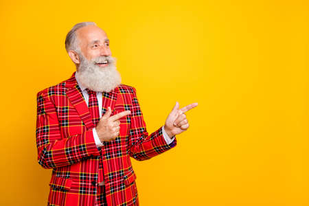 Photo of funny grandpa guy indicating fingers empty space on low prices banner wear lumberjack holiday suit red blazer tie outfit isolated yellow color background