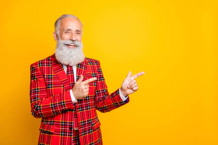 Photo of cool funny grandpa guy indicating fingers empty space salesman wear unusual lumberjack holiday suit red blazer tie outfit isolated yellow color background