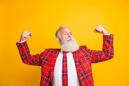 Photo of cool look grandpa model guy raising fists demonstrating amazing biceps self-confident wear red tartan blazer tie clothes isolated yellow color background