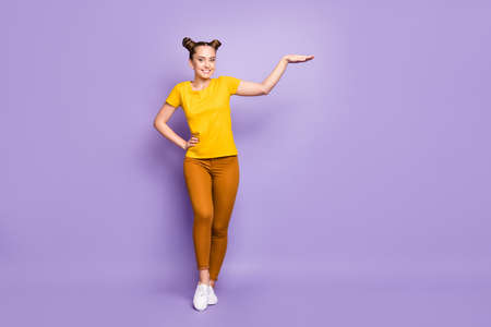 Full body photo of pretty teenager lady holding arm air showing big size length of new promoted product wear yellow t-shirt trousers isolated pastel purple background
