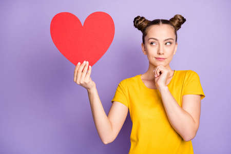 To be or not to be. Photo of amazing lady holding big red paper heart postcard thinking over prom invitation answer wear yellow t-shirt isolated on purple background