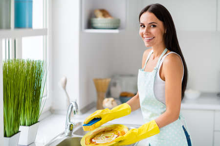 Portrait of positive cheerful girl hold dirty plate want clean wash dishes with yellow sponge wear protective gloves dotted apron in house kitchen light apartment