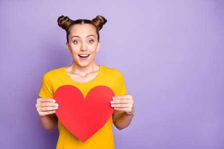 Photo of excited teenager lady holding big paper heart postcard got best prom invitation from boyfriend wear yellow t-shirt isolated on pastel purple background Stock fotó
