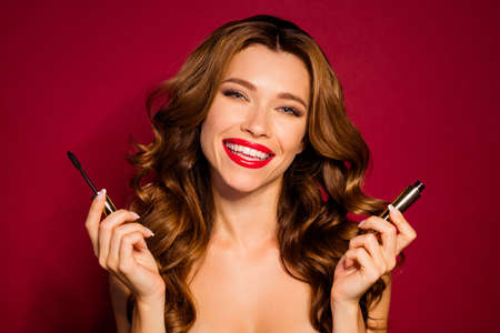 Close up photo of pretty luxury lady with brown wavy hair holding new mascara eyelash bottle and applicator toothy smiling isolated burgundy color background Foto de archivo - 133730500