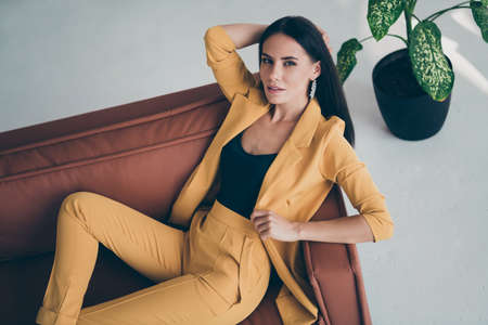 Top above high angle photo of elegant sweet fancy girl lady lie on brown leather couch want attract handsome millionaire man wearing stylish good looking clothes indoors