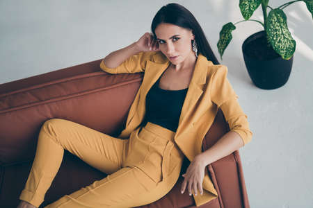 Top above high angle photo of gorgeous beauty rich lady lie on brown leather couch attract millionaire macho men wear stylish yellow vogue outfit in house indoors Фото со стока