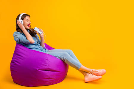 Profile side view of her she nice attractive cheerful cheery wavy-haired girl sitting on bag chair listening music singing song weekend isolated on bright vivid shine vibrant yellow color background