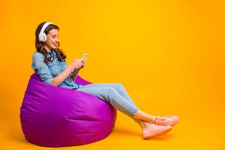 Profiel zijaanzicht van haar, ze is aardig, mooi, vrolijk, vrolijk, golvend meisje, zittend op een zakstoel, luisterend naar moderne muziek, geïsoleerd op een heldere, levendige glans, levendige gele kleurachtergrond Stockfoto