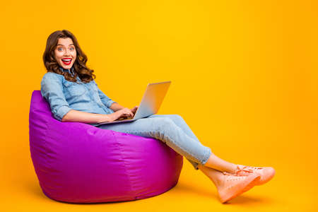 Full length body size turned photo of cheerful cute positive nice pretty girl browsing through computer with excited facial expression and legs crossed isolated over yellow vibrant color background