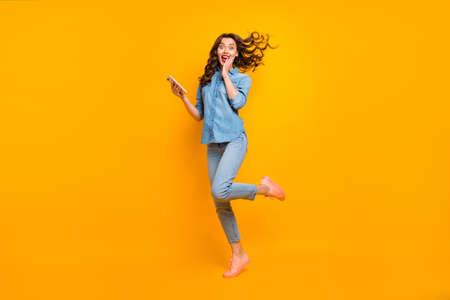 Volledige lengte lichaamsgrootte foto van vrolijke gekke lieve mooie meisjesachtige vrouwelijke jongere dolblij over het ontvangen van lang verwacht bericht met telefoon die emoties uitdrukt geïsoleerde levendige kleurenachtergrond