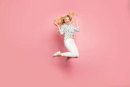 Full length body size photo of turned cheerful positive cute excited crazy woman jumping throwing up her hair isolated pastel color background