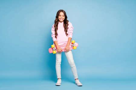 Ganzkörperfoto in voller Länge von fröhlichem, positivem rosa Schulkind, das Skateboard hält, fröhlich lächelnd isoliert pastellblauer Farbhintergrund Standard-Bild