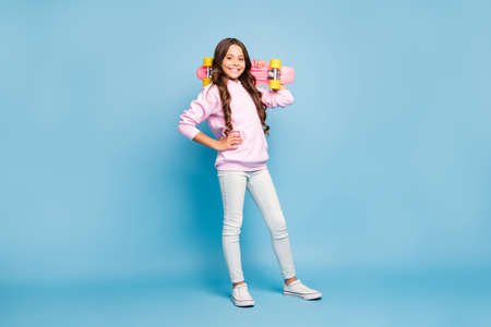 Turned full length body size photo of cheerful pink positive girl holding skate board on her shoulder wearing footwear isolated pastel blue color background