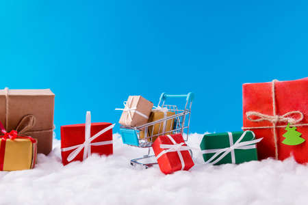 Many x-mas small red green yellow brown gift boxes stay inside supermarket trolley x-mas time christmas season shopping concept stand under blue sky background Stockfoto