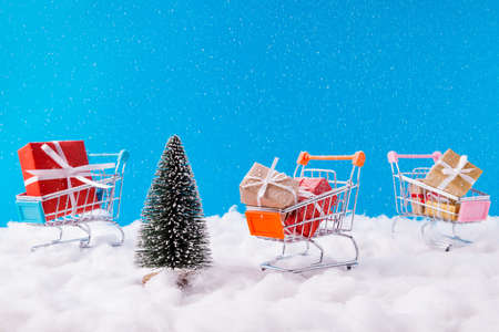 Christmas discounts concept. Photo of three santa claus unusual metal trolleys loaded giftboxes new transportation idea service newyear winter snowy colorful background