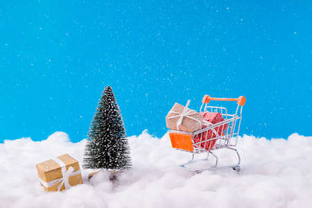 Christmas shopping concept. Photo of santa claus creative metal trolley loaded giftboxes new idea transportation service newyear advertisement winter snowy background Stockfoto