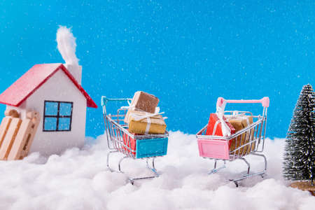 Little white house with smoke flying from chimney charming couple living buying product have supermarket trolley holding yellow red brown giftboxes stand under sky blue background