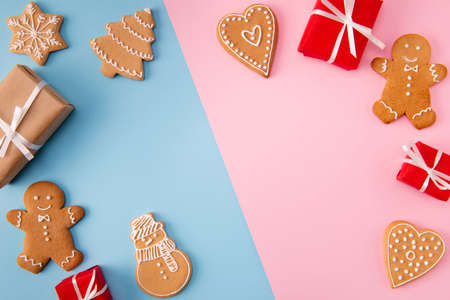 High angle above view photo of divided into two pink blue color parts background decorated sweet holiday biscuits figures giftboxes x-mas greeting postcard idea composition