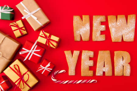 High angle above view photo of surprise newyear biscuits congrats two baked words decor figures tasty x-mas composition giftboxes candies isolated bright red background