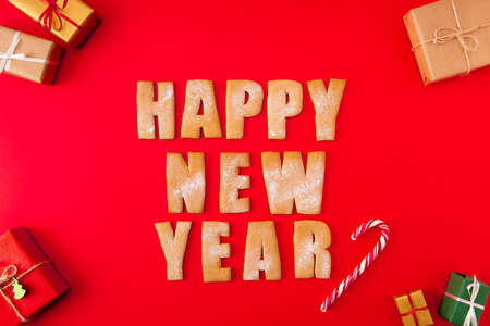 High angle above view photo of surprise newyear biscuits congrats words decor figures tasty yummy x-mas composition giftboxes candy isolated bright red background