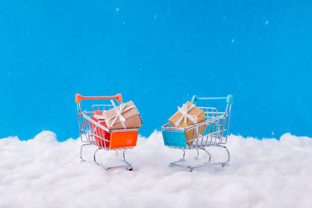 X-mas season shopping sales noel concept. Little toy supermarket trolley having yellow brown red gift stand under snow fall snowflakes blue sky background Stockfoto