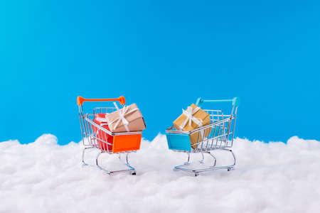 Little toy supermarket trolley have yellow brown red giftboxes with white ribbons christmas x-mas season tradition shopping concept stand under blue sky background