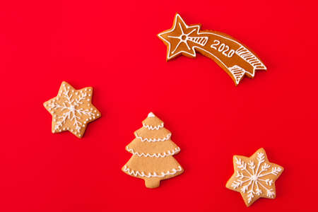 Top above high angle view photo of composition gingerbread cookies christmas tree star falling with 202o text prepared for x-mas celebration party lie isolated over red color background
