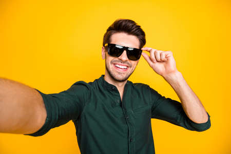 Close up photo of positive cheerful guy rich wealthy son of millionaire travel trip blogging feel candid have fun tale selfie touch spectacles wear modern clothing isolated yellow color background