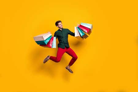 Foto del tamaño del cuerpo de cuerpo entero de un hombre saltador guapo positivo alegre sosteniendo numerosos paquetes que regresan del centro comercial aislado fondo de colores vivos