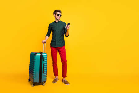 Full size profile side photo of cheerful traveler guy on summer vacation reach destination hold package use cellphone reserve taxi wear green shirt pants trousers isolated yellow color background