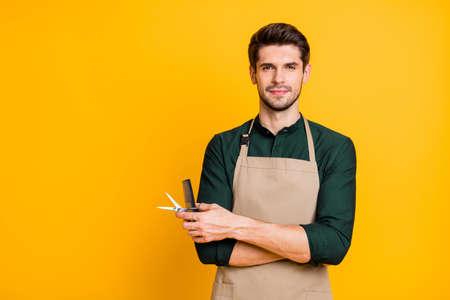 Portret poważnego profesjonalnego faceta trzyma nożyczki grzebień gotowy do zrobienia wspaniałej fryzury nosić w stylu casual zielona koszula na białym tle nad jasnym kolorem tła Zdjęcie Seryjne