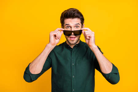 Portrait of astonished guy hear incredible news touch his sunglass scream wow omg wear casual style outfit isolated over yellow color background