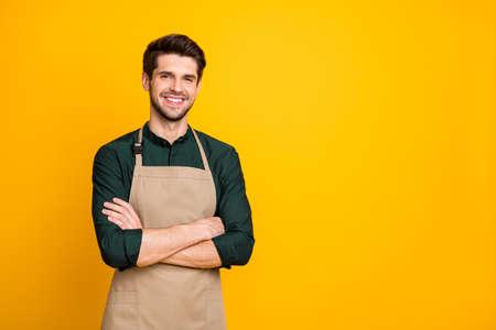 Foto de blanco alegre hombre positivo sonriendo toothily con los brazos cruzados expresando emociones positivas en la cara cerca del espacio vacío aislado de fondo de color brillante