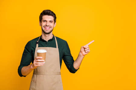 Portrait of positive cheerful guy freelancer own coffee bar shop hold paper card cup point index finger indicate sales discounts wear stylish trendy green shirt isolated over yellow color background 스톡 콘텐츠