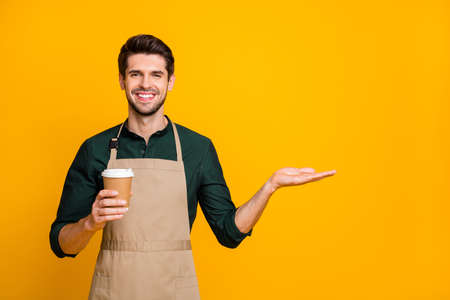 Photo of cheerful trendy stylish handsome attractive man advising you to visit his coffee house smiling toothily isolated over vivid yellow color background Imagens