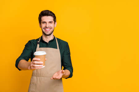 Here your latte. Portrait of positive cheerful guy student work part-time in coffee bar shop give to client paper card disposable mug wear stylish trendy outfit isolated over yellow color background