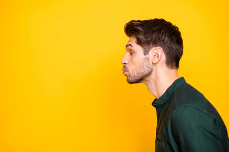 Side profile photo of tender man full of feelings pouting his lips to kiss empty space next to him with eyes closed in a fit of imaginary dreams isolated vibrant color background