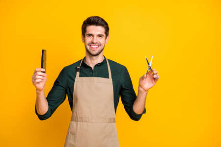 Portrait of positive cheerful guy freelancer ready to make haircut to his clients in modern barbershop hold comb scissors wear stylish trendy green shirt isolated over yellow color background 스톡 콘텐츠